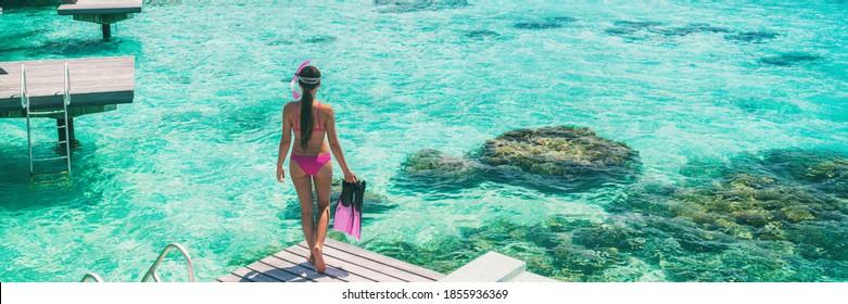 Luxury beach vacation Bora Bora resort woman going snorkeling with snorkel fins swimming from overwater bungalow panoramic. Tahiti paradise destination vacation.