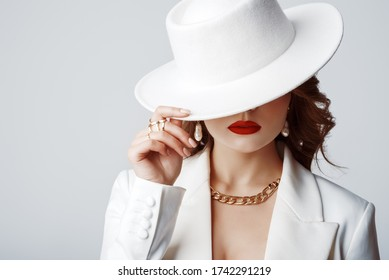 Luxury beautiful fashionable woman wearing stylish accessories: earrings, rings, chain, white hat. Hidden eyes. Female fashion, beauty, advertising concept. Close up studio portrait. Copy, empty space