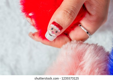 luxury beautiful woman acrylic fingernail painting cute Santa Claus design for celebrated in Christmas holiday
