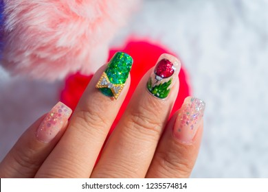 luxury beautiful woman acrylic fingernail painting sparkling Christmas ball gel nail art decorated with shiny gold ribbon on green glitter design for celebrated in holiday