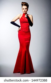 Luxury. Beautiful woman in black gloves and sleeveless red dress