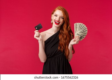Luxury, beauty and money concept. Elegant good-looking redhead woman being rich, wear luxurious black dress, holding credit card and fan of dollars, brag her income, smiling carefree