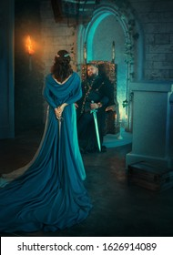 Luxury beauty Queen turned away. medieval royal creative clothes. Lady holds gothic dagger back. Blue cloak cape. Backdrop old retro room. Strong adult men king sits on throne. Dangerous conspirator