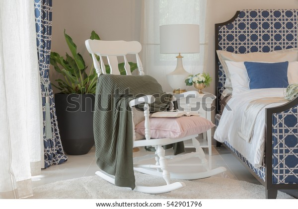 luxury bedroom in blue color tone with white wooden rock chair, interior design