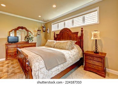 Luxury bedroom with carved wood bed, nightstand, vanity cabinet with mirror and decorative lanterns