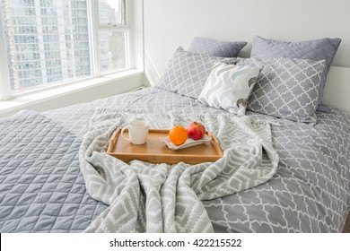Luxury bedroom. Contemporary design with reclaimed wood bedside tables and lamp. Nice and cozy accommodations. Hotel or resort room. Vancouver downtown view.