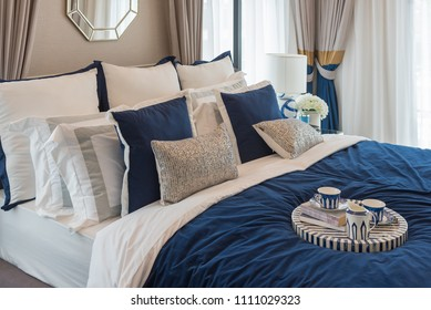 luxury bedroom in indigo blue tone with set of tea cup on wooden tray, interior design decoration concept
