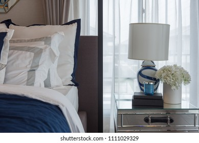 luxury bedroom in indigo blue tone with classic lamp and vase of plant on table side, interior design decoration concept