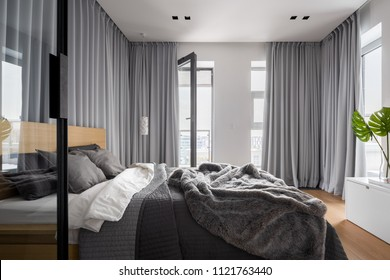 Luxury bedroom interior with double bed and gray window curtains