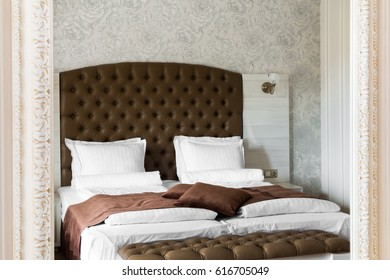 Luxury bedroom interior reflected in a mirror with a neat double bed with large brown upholstered headboard and a matching throw and ottoman at the foot in a classic room with patterned wallpaper