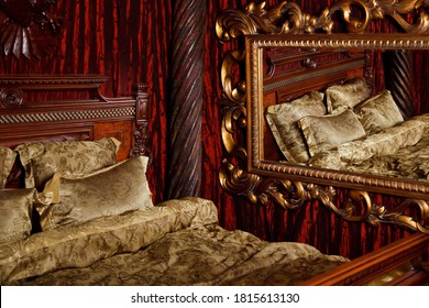 Luxury bedroom in medieval style with art Deco elements and large mirror. Bed and items with patterns. Refined interior. Comfortable king size bed in gold color. Copyright space for website or banner