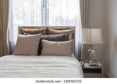 luxury bedroom with set of pillows and classic lamp on table side, interior decoration design concept