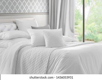 Luxury bedroom that opens with French doors onto a terrace. King bed with white linens and pillows. Interior with garden view window, bed with white bed linen and curtains.