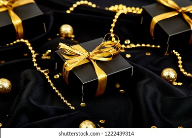 Luxury black gift boxes with gold ribbon on shine background. Christmas, birthday party presents. Flat lay. Copy space. Top view.