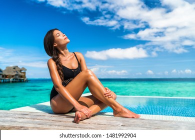 Luxury Bora Bora vacation hotel woman sunbathing relaxing at overwater bungalow suite in Tahiti resort, French Polynesia travel destination.