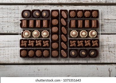 Luxury Box of Assorted handmade chocolate truffles on white wooden rustic background. Chocolates in different shapes and colors in paper box. Above angle view. Copy space for text area.