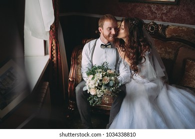luxury bride in vintage dress with bouquet and stylish groom embracing and smiling at window in morning light in hotel room. happy wedding couple, sensual romantic moment,
