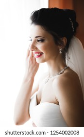 Luxury bride in white dress posing while preparing for the wedding ceremony