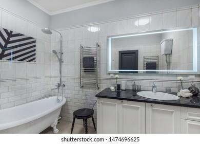 Luxury bright bathroom with sink, mirror and tub