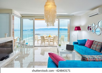 Luxury bright interior of villa living room with marble floor with sea view with  modern color furniture flat screen tv, laptop and terrace Bodrum Turkey - Sucessful sea life concept or work at home