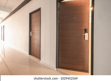 Luxury brown wooden door with electronic lock and viewer in hotel corridor
