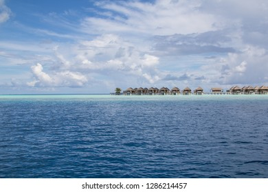 Luxury bungalows of a hotel on a shallow reef crest on a Maldives island