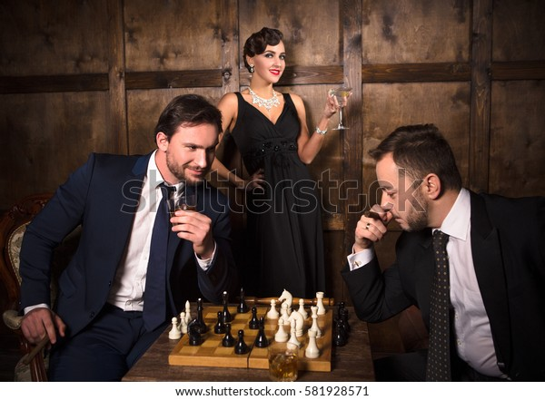 Luxury business concept. Two rich men playing chess in expensive restaurant while elegant lady smiling and waiting for one of them.