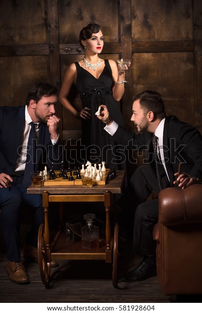Luxury business concept. Two rich men playing chess. One executive showing to his partner white chess piece and saying something. Elegant lady is on background.