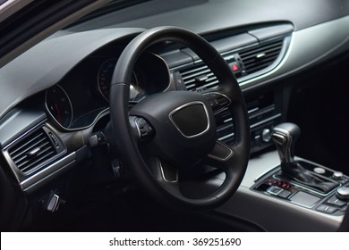 luxury car black leather and brushed aluminium interior inside view with automatic transmission, GPS screen, steering multifunctional wheel, indicators, climatisation dashboard close up.