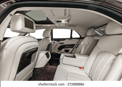 Luxury car inside. Interior of prestige modern car. Back seats with displays & wood decoration. White cockpit with panoramic roof on isolated white background.