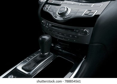 Luxury car inside. Interior of prestige modern car. Automatic transmission gear shift. Black perforated leather cockpit. Media control buttons in black leather with navigation computer monitor screen