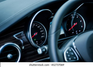 Luxury car interior details. Speedometer and steering wheel