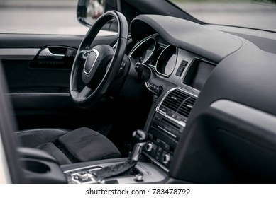 Luxury car interior. Steering wheel, shift lever and dashboard.