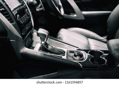 Luxury of car interior at transmission shift gear area. Modern car interior, gearstick radio and cup holder.