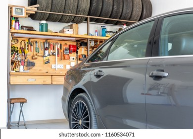 Luxury car parked at large spacious private home garage. Big wooden workbench with lot of tools at background. Spare season wheels storage. DIY, self service and repair