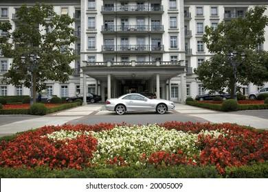 Luxury car parked outside a hotel in Swiss with flower-garden