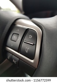 Luxury car steering wheel close-up control buttons.