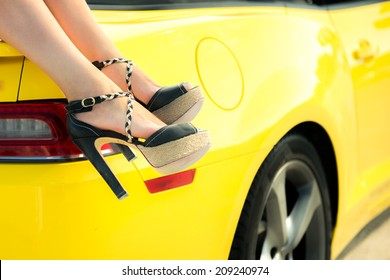 Luxury car travel concept background. Woman feet against a luxury car. Summer vacations concept.