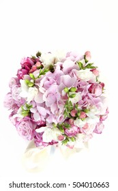 Luxury celebratory bouquet of various flowers in a pink gift box decorated with a bow - hydrangeas, roses. On a white background