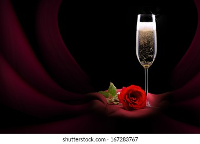 luxury champagne glass with red silk and flower on black background