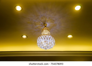 The luxury chandelier with beauty lighting on the golden ceiling and 4 lights around.
