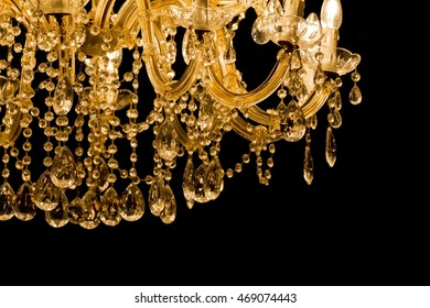Luxury chandelier with light candles and right dark background. Noble candelabra hanging on ceiling with lots of little gems