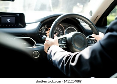 Luxury Chauffeur in Suit Holding Steering Wheel Safely while Driving on Modern Car. Limousine Services