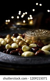 Luxury chocolate coated almonds, hazelnuts, cashew nuts and cherries shot against a dark festive background with generous accommodation for copy space.