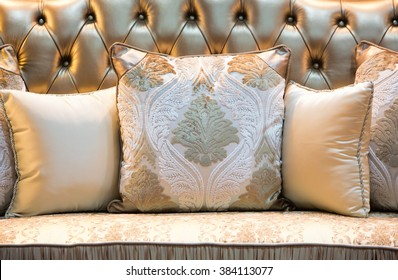 Luxury and classic style pillows on a shiny leather sofa.