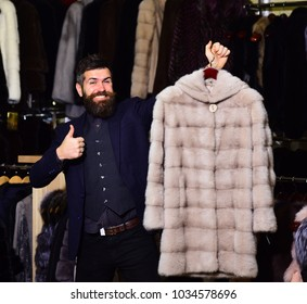 Luxury clothing concept. Guy holds beige furry coat in shop with fur on background. Man with beard holds fur coat showing thumbs up. Macho with stylish appearance with mink fur in fashion store.