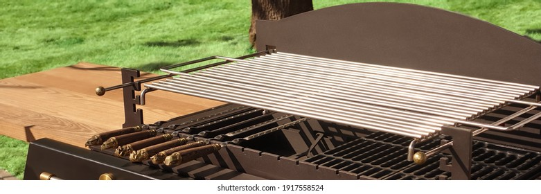 luxury Combo Grill Table On Backyard. Outdoor Backyard Kitchen Table With BBQ Charcoal Grill Appliance. Family Garden Party Barbecue Grill, Closeup View, Green Backyard Lawn In The Background.