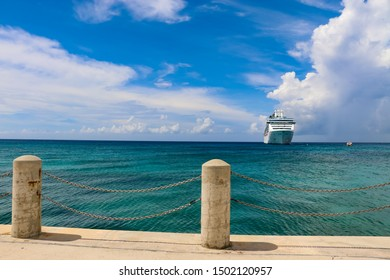 Luxury cruise ship anchored in blue ocean waters of Grand Cayman in a sunny blue sky day