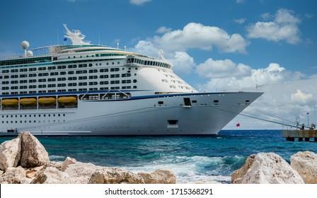 Luxury cruise ship beyond rock sea wall in Curacao