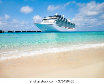 Luxury cruise ship docked at tropical Caribbean beach.